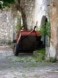 Röd bilsläp bredvid övergav gamla byggnader på den lappade vägen i Bakar, Kroatien Royaltyfria Bilder