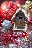 Röd bollar, bird-house, snowflakes och sn för jul Arkivfoton