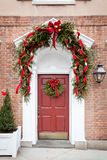 Röd dörr med julkransen Arkivfoto