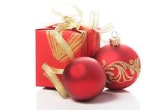 Röd gåvaask med guld- band och xmas-struntsaker Arkivfoton