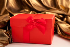 Röd gåvaask med lyxigt guld- tyg Arkivfoto