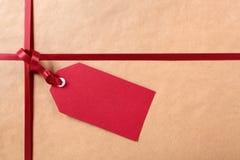 Röd gåvaetikett och band, brun bakgrund för inpackningspapper Arkivfoton