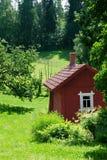 Röd idyllisk stuga i sommarliggande Royaltyfri Bild