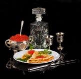 Röd kaviarang-vodka på svart Arkivfoto
