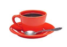 Röd kopp kaffe på plattan och skeden som isoleras på vit Arkivfoton