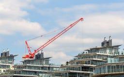 Röd kran och moderna byggnader Arkivbilder