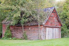 Röd ladugård med ett blått tak Arkivfoton