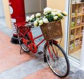 Röd målad cykel med en hink av vita blommor Arkivfoto