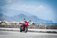 Röd motorcykel nära havskustlinjen på den Paleochora staden på Kretaön Arkivbilder