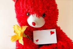 Röd nallebjörn som rymmer en anmärkning Arkivfoto