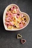 Röd och gul hjärta formad pasta i hjärtaformramekinen, överkant VI Arkivfoto