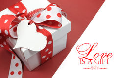 Röd och vit ask för pricktemagåva som är närvarande med etiketten för hjärtaformgåva, med förälskelse, Royaltyfri Bild
