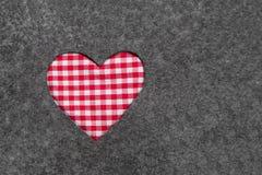 Röd och vit rutig hjärta på grå filtbakgrund Fotografering för Bildbyråer