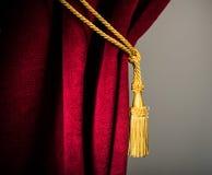 Röd sammetgardin med tofsen Royaltyfri Foto