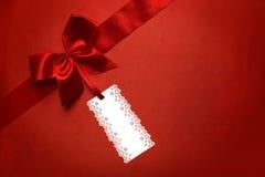 Röd siden- torkdukebakgrund med etikettsetiketten och bandpilbågen, gåva Arkivfoto