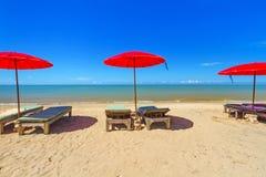 Röd slags solskydd med deckchair på den tropiska stranden Arkivbilder
