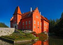 Röd slott för saga på sjön, med mörker - blå himmel, tillståndsslott Cervena Lhota, Tjeckien Arkivbild