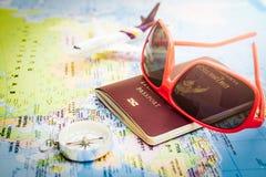 Röd solglasögon, pass, kompass och flygplan på den Europa översikten Arkivbilder