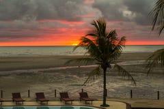 Röd solnedgång på en tropisk strand i en simbassängsemesterort Arkivfoto