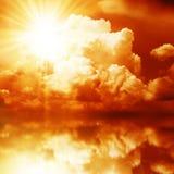 Röd solstråle i de mörka molnen Arkivbilder