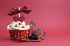Röd temamuffin med förälskelsehjärta och fjäril på röd bakgrund Arkivfoto