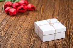 Röd tulpanbukett och en gåvaask på en trätabell Arkivfoton