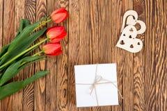 Röd tulpanbukett och en gåvaask på en trätabell Arkivbilder
