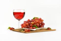 Röda druvor och rött vin Arkivfoto