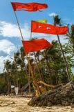 Röda flaggor på tropisk vit sand sätter på land med palmträdFilippinerna Arkivbild