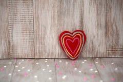 Röda Fuzzy Handmade Heart på tappningträbakgrund Arkivfoton
