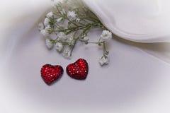 Röda hjärtor på kräm- tyg Fotografering för Bildbyråer
