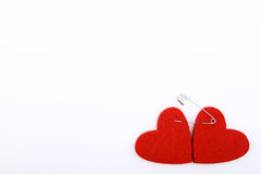 Röda hjärtor som klämmas fast med en säkerhetsnål Arkivbild