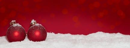 Röda julstruntsaker i snön Royaltyfria Foton