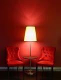 Röda lyxstolar med tabellen och lampan Royaltyfri Foto