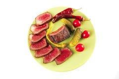 Röda nötköttskivor på grön maträtt Royaltyfria Foton