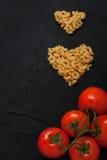 Röda nya tomater och svart för pastahjärtaform hårdnar backgrou Royaltyfria Foton