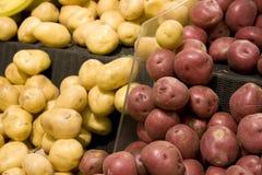 Röda och gula potatisar i livsmedelsbutik Arkivfoto