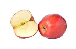 Röda äpplen för helhet och för halvt snitt med stammen på vit Arkivbild