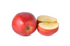 Röda äpplen för helhet och för halvt snitt med stammen på vit Arkivfoto