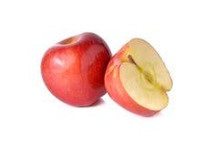 Röda äpplen för helhet och för halvt snitt med stammen på vit Royaltyfri Bild