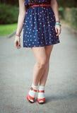 Röda sandaler med vita sockor på flicka lägger benen på ryggen i femtiotalstil Fotografering för Bildbyråer
