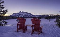 Röda stolar på denstålar sjön Arkivbild