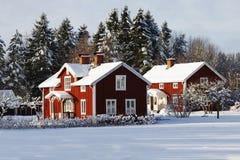 Röda stugor, lantgård i snöig vinterlandskap Royaltyfri Foto