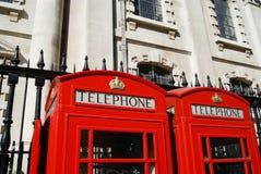 Röda telefonaskar i London, England Arkivbilder