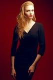 Rödhårig (ljust rödbrun) trendig modell i svart klänning Fotografering för Bildbyråer