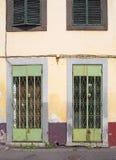 rdzewieć zielonych metali drzwi z ozdobną kratownicy pracą na przodzie wykolejeniec porzucający sklep z zatartymi koloru żółtego  zdjęcia stock