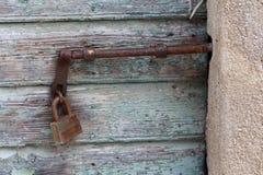Rdzewiejąca metal zapadka wspinająca się na drewnianych desek drzwiach blokujących z stronniczo rdzewiejącą kłódką otaczającą z b zdjęcie royalty free