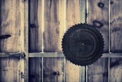 Rdzewiejąca kurenda Zobaczył ostrza na Drewnianej ścianie - Retro zdjęcia stock