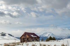 Rdzewieję zadaszał beli kabinę w Idaho pustkowia zimie z clou Obraz Stock