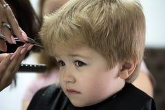 Reírse el corte de pelo Corte de pelo dado del pequeño niño Pequeño niño en salón de la peluquería Niño pequeño con el pelo rubio foto de archivo